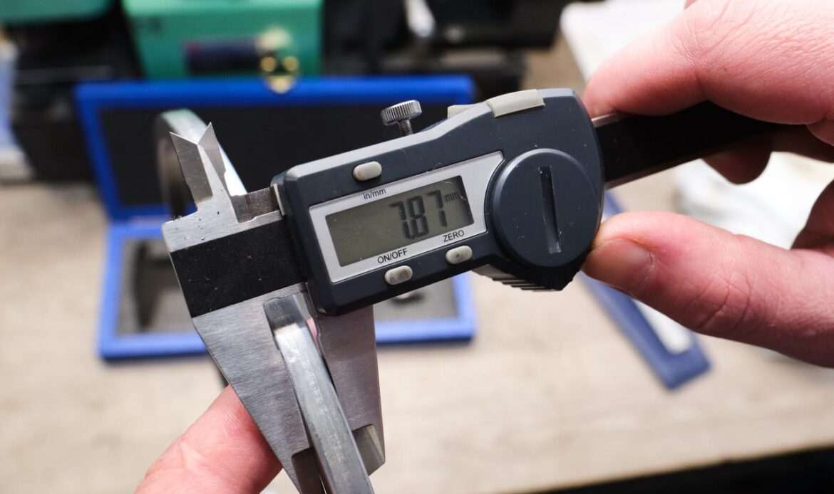 The process of measuring the thickness of a ring of a diesel engine using a caliper with a digital scale. In the background, manufacturing details in blur. Quality control